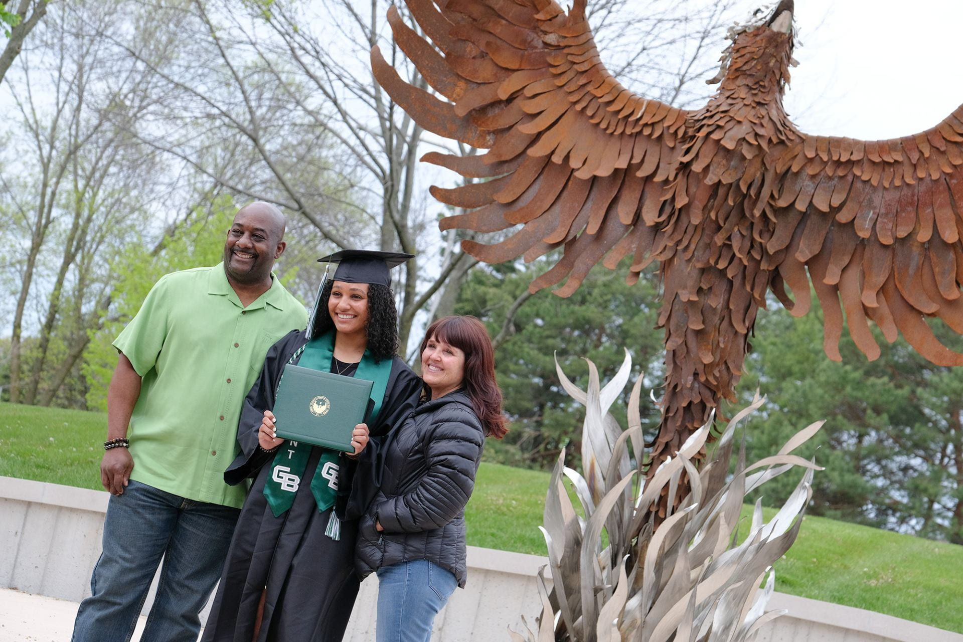 Graduate and family posing in front of the Phoenix Rising sculpture
