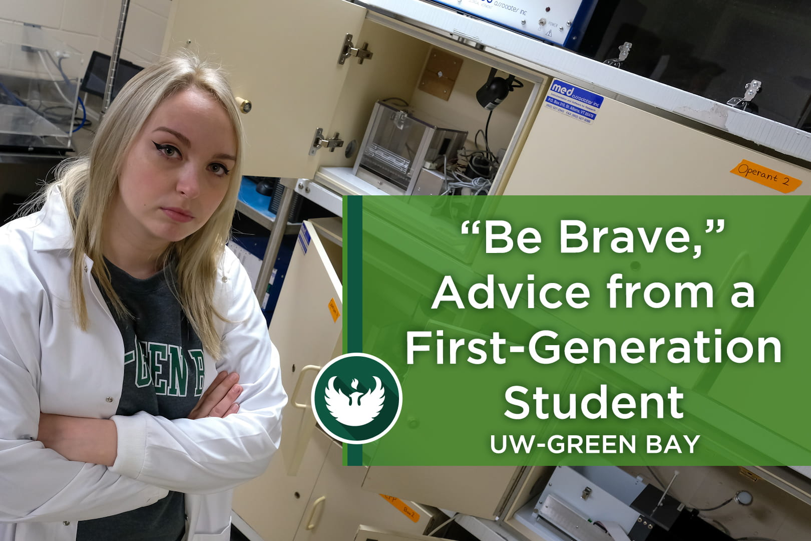 Photo of UW-Green Bay's Paige Anderson is a resilient first-generation psychology student, posing in the PANE Lab, wearing a white lab coat in front of the testing station.