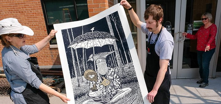 """Two artist carry a large relief print that depicts a person sitting on the ground holding a bird underneath an umbrella with text, """"We are all in this together...hold with care...nurture nature and a life is..."""""""