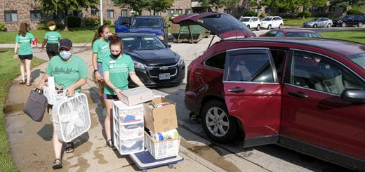 Photo of volunteer students loading a cart with boxes from a car to help an incoming new student move into the dorms outside Roy Downham Hall at the UW-Green Bay campus.