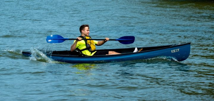 A student having fun kayaking canoeing on the Bay of Green Bay during GB Week's Boats on the Bay event.
