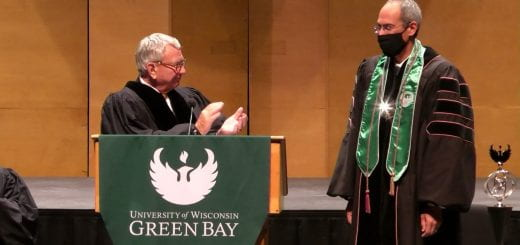 Interim UW System President Tommy Thompson claps after putting the Chancellor medallion around Chancellor Michael Alexander's neck during the Installation of Michael Alexander, the seventh Chancellor of UW-Green Bay on Thursday, September 30, 2021.