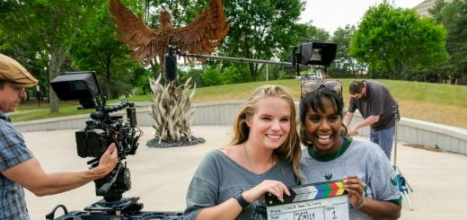 From left, UW-Green Bay students Emily Reis and Soundarya Ritzman, pose with the video clapper board after the filming of UW-Green Bay's commercial PSA in front of the Phoenix sculpture at the UW-Green Bay, Green Bay Campus. Photo by Sue Pischke, University Photographer.