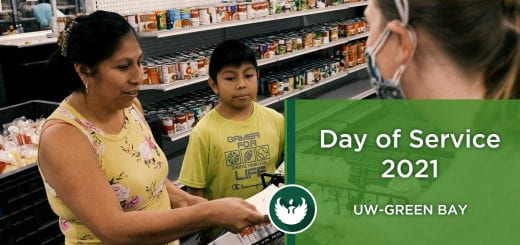 UW-Green Bay staff member helps a mother and her son find groceries at Paul's Pantry during the Day of Service event in Green Bay on Friday, Oct. 1, 2021.