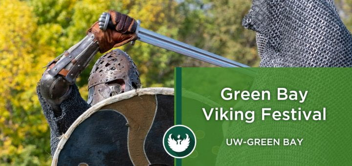 Photo of two men dressed as Vikings battling with swords during a Viking battle reenactment during the Viking Festival at UW-Green Bay.