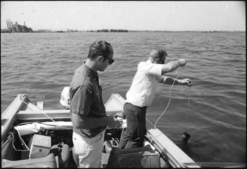 Two men in an outboard fishing boat conducting water tests