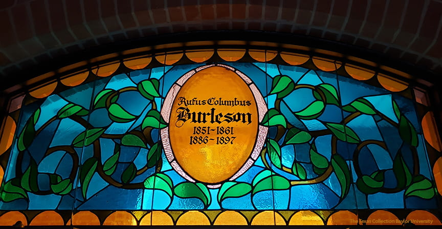 Half moon shaped stained glass transom window depicting the years served of Baylor President Rufus C. Burleson that can be found in Bennett Auditorium.