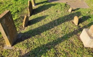 aged and broken headstones closely aligned