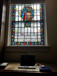 Graduate Assistant Desk and laptop. Stained glass window depicting Robert Browning's Ferishtah's Fancies above desk.
