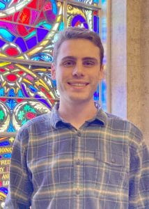 Male young adult standing in front of a stained glass window.
