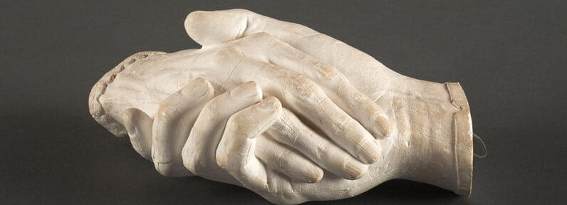 A sculpture of a man and woman's hands clasped together.
