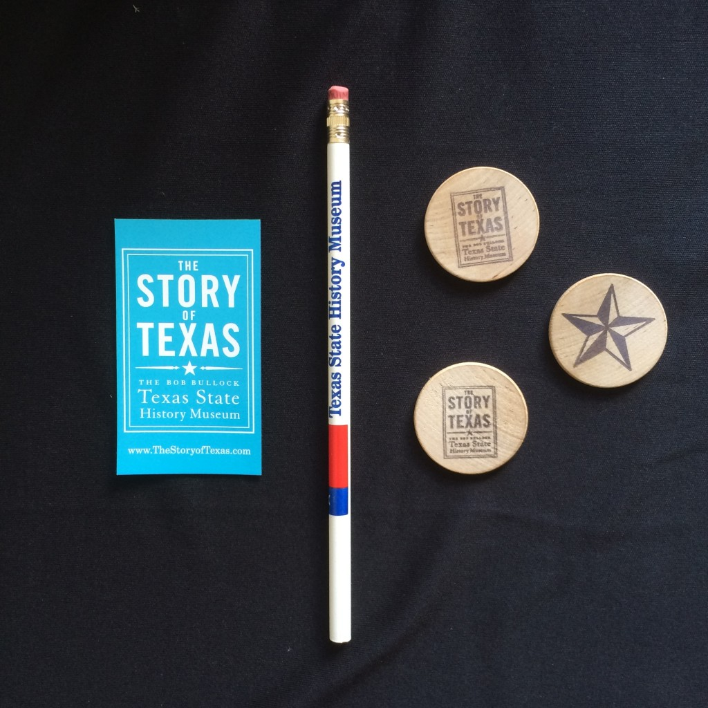 A commemorative magnet, pencil and wooden nickels from the Bullock Museum.