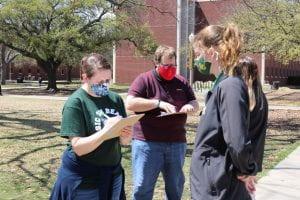 Photo of staff members registering students.