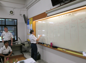 A Thai cadet participates in class, learning new English vocabulary and grammar.