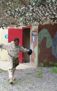 Cadet Hagood walks out of the gas chamber after breathing in CS gas. She was instructed to immediately start fanning her arms up and down and continually spit out any chemical residue breathed in.