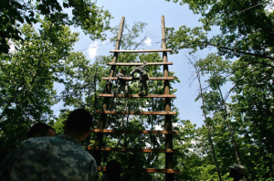Cadets from the 6th Regiment climb up, unaided and unattached, a high, spaced out wooden ladder.