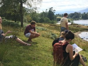 Students read and discuss poems on the shore of a lake in Grasmere, England