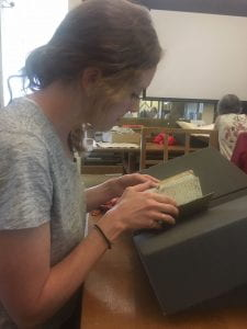 A woman reads a book propped up on foam blocks.