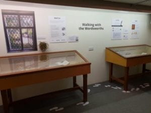 """A museum exhibit with two display cases and posters on the wall between with the words """"Walking with the Wordsworths."""" There are paper footprints on the ground creating a trail around the display cases."""