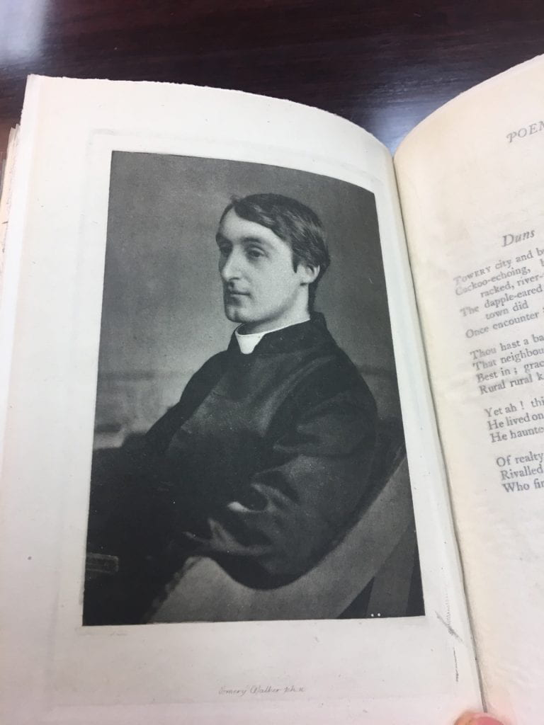 Image from a book of Gerard Manley Hopkins in profile and sitting in a chair. He has dark hair and is wearing a white priest's collar..