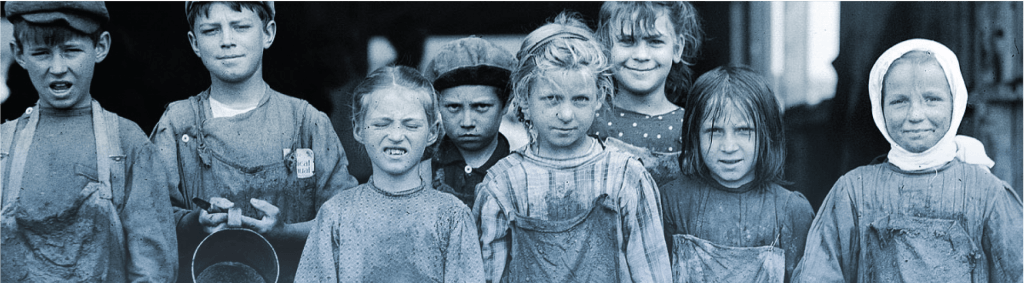Black and white image of eight children wearing dirty clothing from the 19th century. They are all face the camera in a line, some smiling and some frowning.