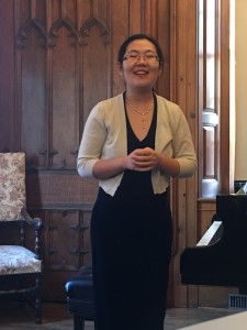 Ms. Wang welcomes audience members and invites the children to sit in front to more easily view the pictures during the second piece.