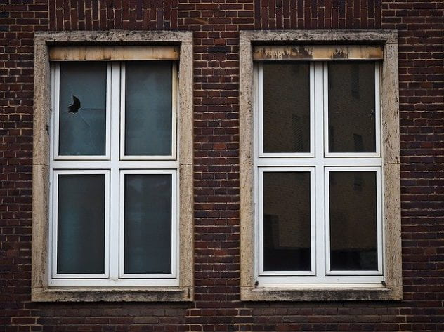 Two windows. one is tinted blue and has a crack, the other is tinted yellow.