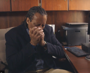 Dr. Harris sitting at his desk playing blues harmonica.