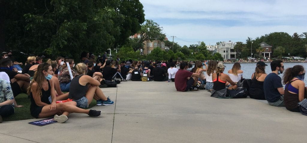 Demonstrators sit at Colonial Lake