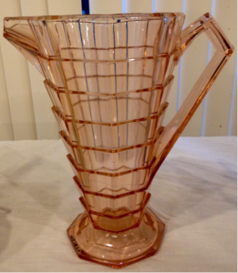 Depression class, c. 1926. Pink depression glass pitcher on an octagonal foot; body tapers from top to bottom in a series of eight rings, eight sections in each ring. Angular spout and angular handle. Inside wall of pitcher is rounded.