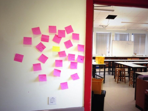 Post-it notes with students' feedback about the class stuck to the wall outside the classroom door.