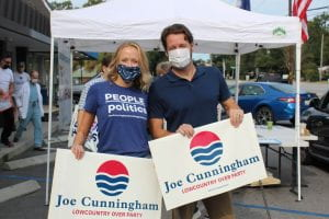 Allie Watters and candidate Joe Cunningham holding campaign signs