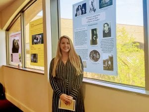 "Meg Dunavant standing in front of her poster, ""Words from a Loving Father: a Defense for Yates' 'A Prayer for my Daughter'"""