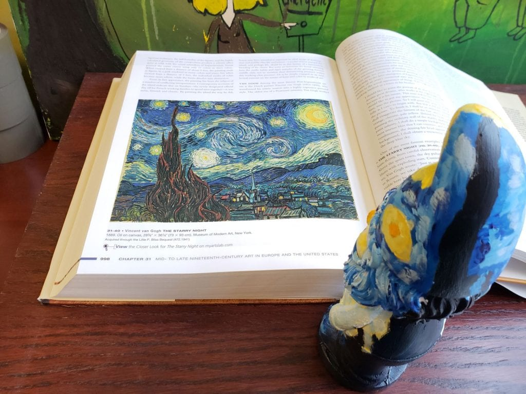 a small garden gnome painted to resemble Vincent van Gogh's Starry Night standing as if looking at a picture of Starry Night in a book