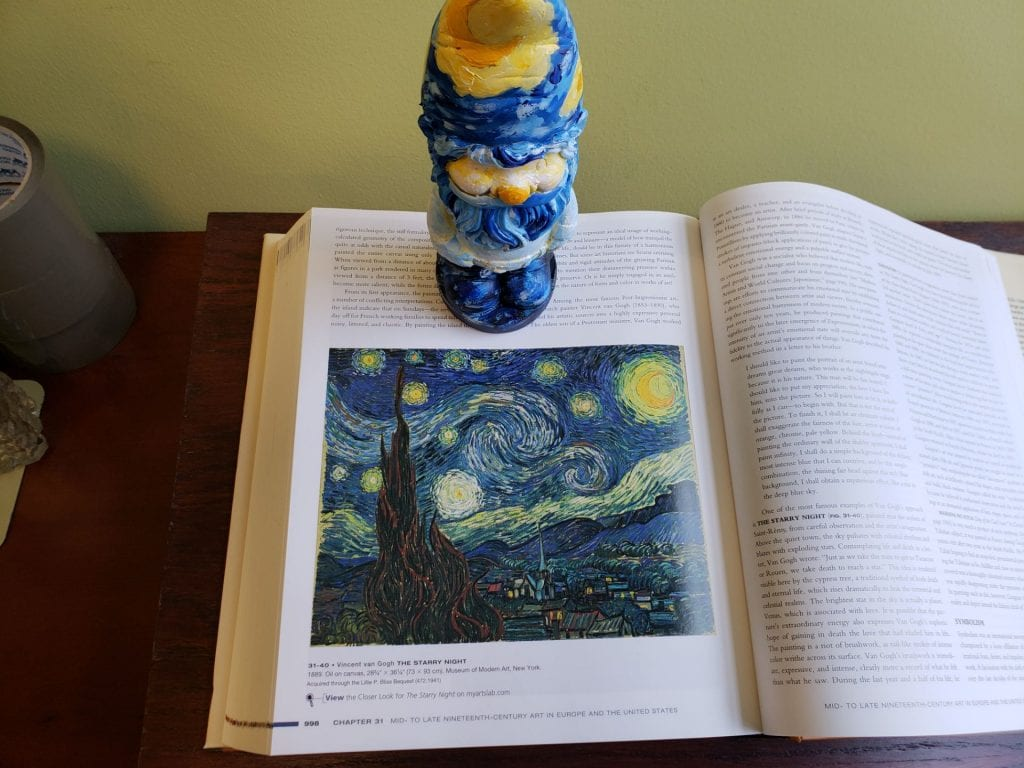 a small garden gnome painted to resemble Vincent van Gogh's Starry Night standing near a picture of Starry Night in a book