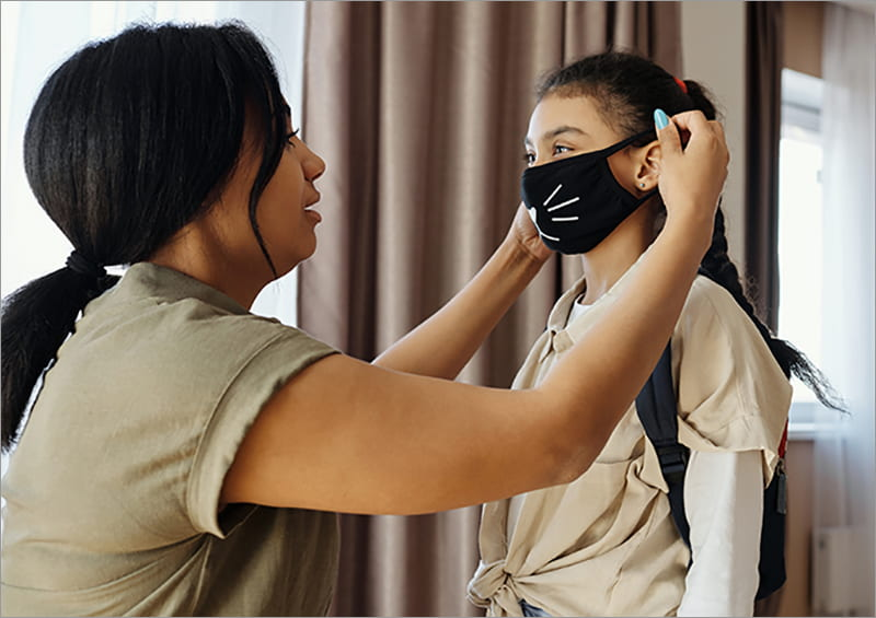 Parent putting on child's face mask