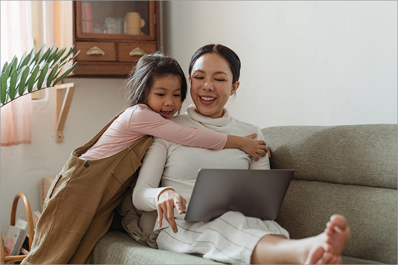 parent and child with laptop on couch
