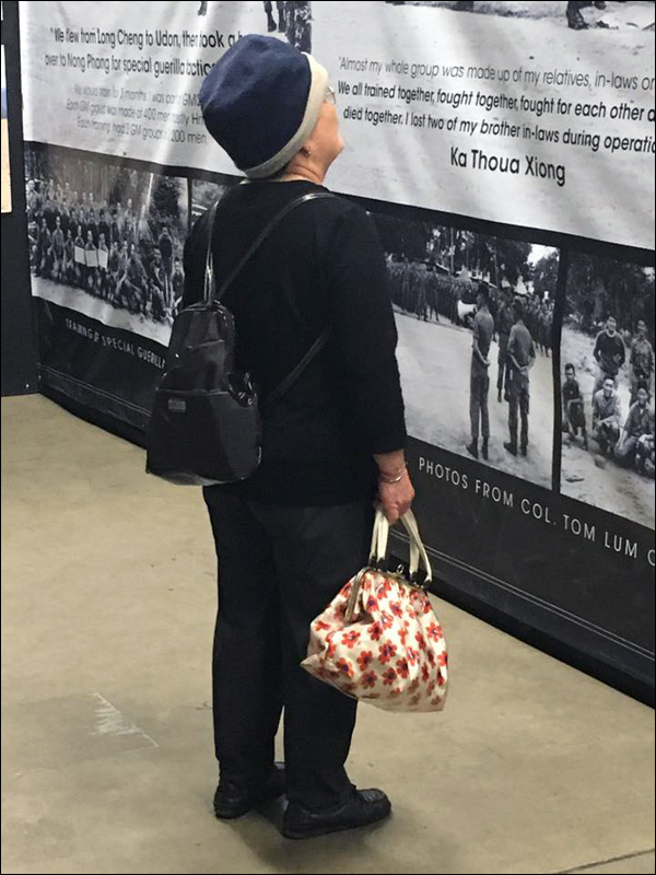Exhibit attendee reading about the different refugee camps