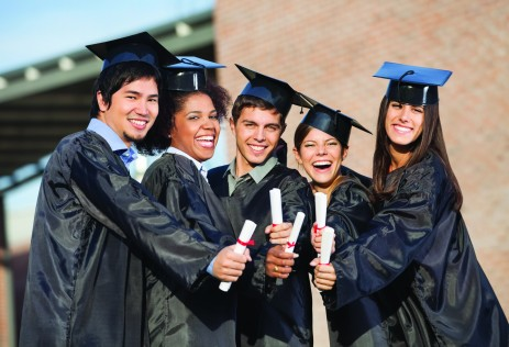 Portrait of happy students in graduation gowns showing diplomas