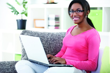 Photo of African woman using laptop at home