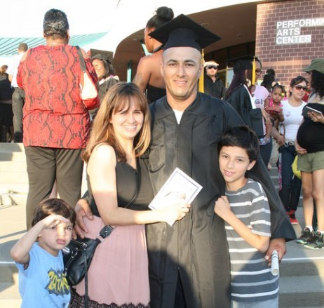 Photo of a GED completer with his diploma and his family.