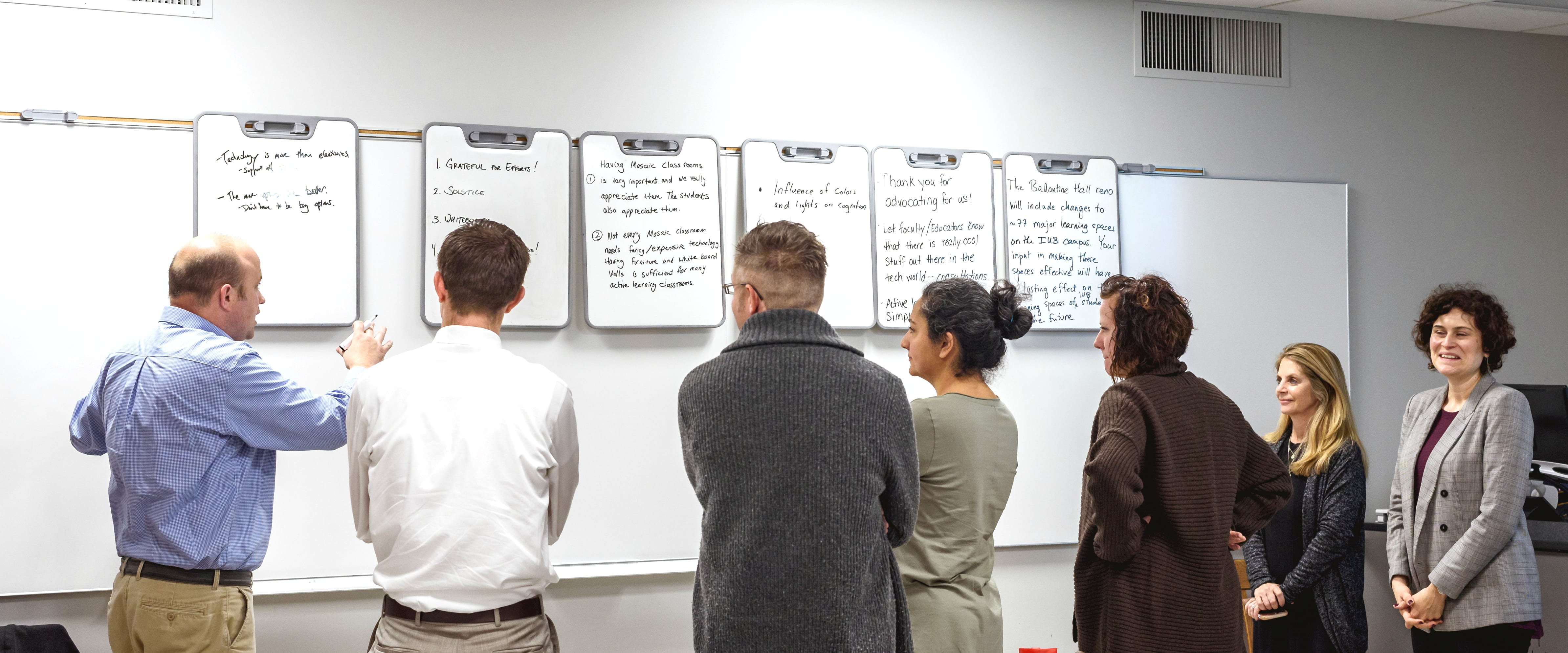 Mosaic Faculty Fellows join Director Julie Johnston in conversation around verb boards that have the written feedback