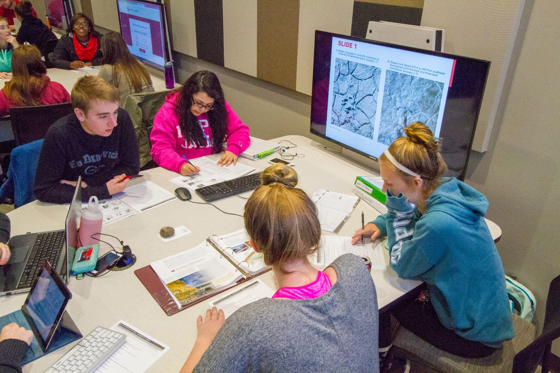 A group of 5 students collaborate at their group table in IUPUI's Lecture Hall LE 104