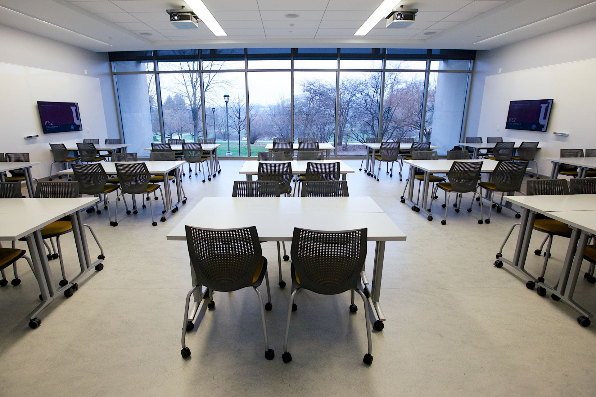 Student tables and chairs are organized in the space to create groups of four.