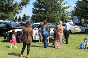 Families play on the mosque's front lawn as representatives from the local fire department, police department, and city government talk with ICGT members at the 2019 International Festival.