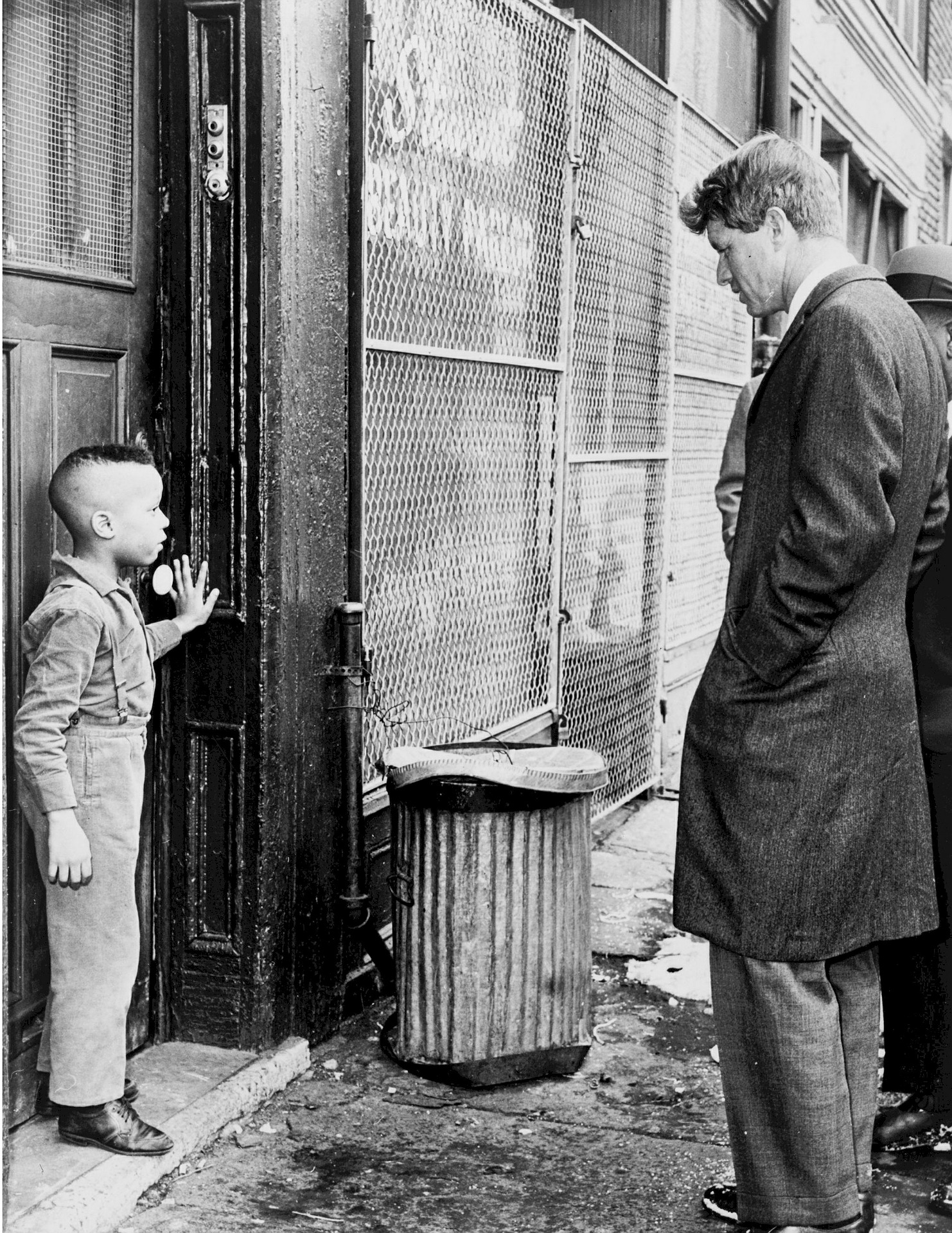 Robert Kennedy talking to young boy in the street.