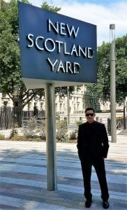 Elias Rebollar standing in front of a sign that says New Scotland Yard.
