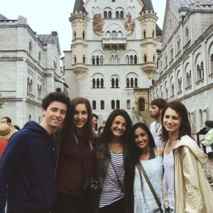Group of students participating in SPEA Abroad stand in front of historic buildings.