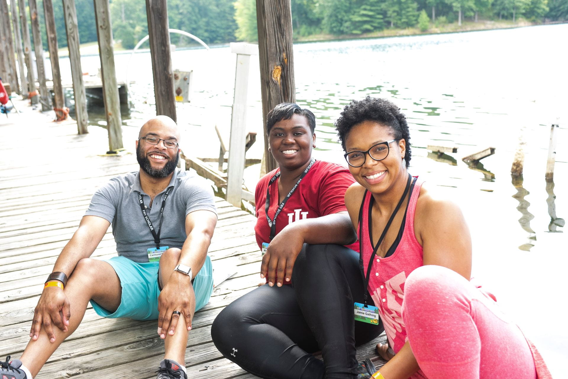 KODI advisors Carmund White, Maqubè Reese, and Jamie Gathing sit on a dock with water in the background.