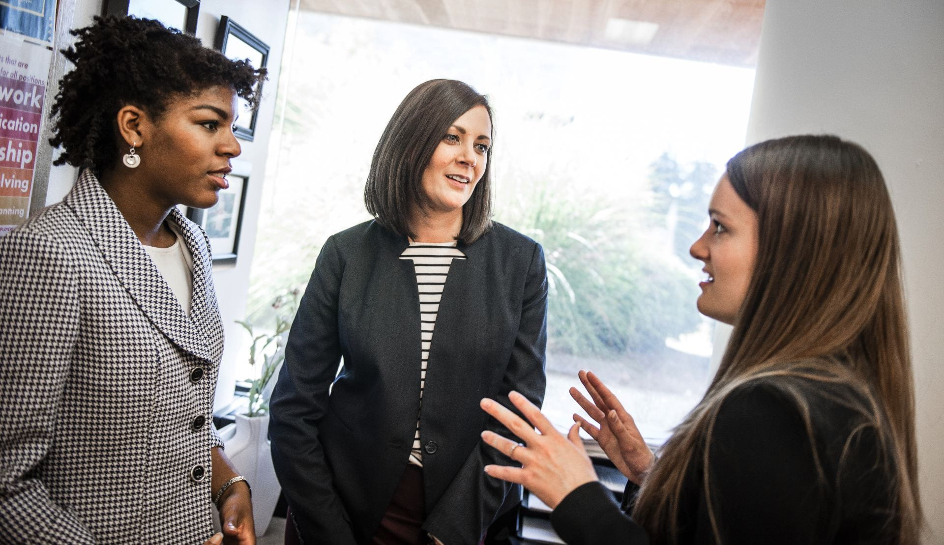 Three women, including a company, recruiter have a conversation while standing